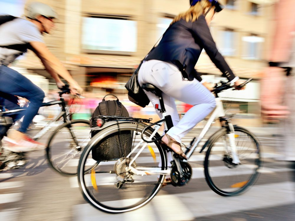Woman biking on downtown road