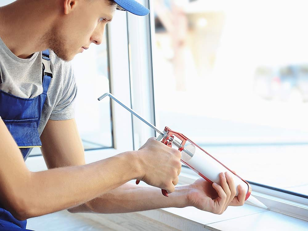 Man using caulk-tube to repair window
