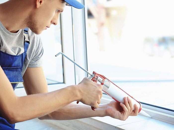 Man using caulk-tube to repair window
