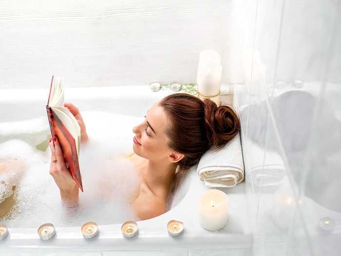Woman taking a bath with candles