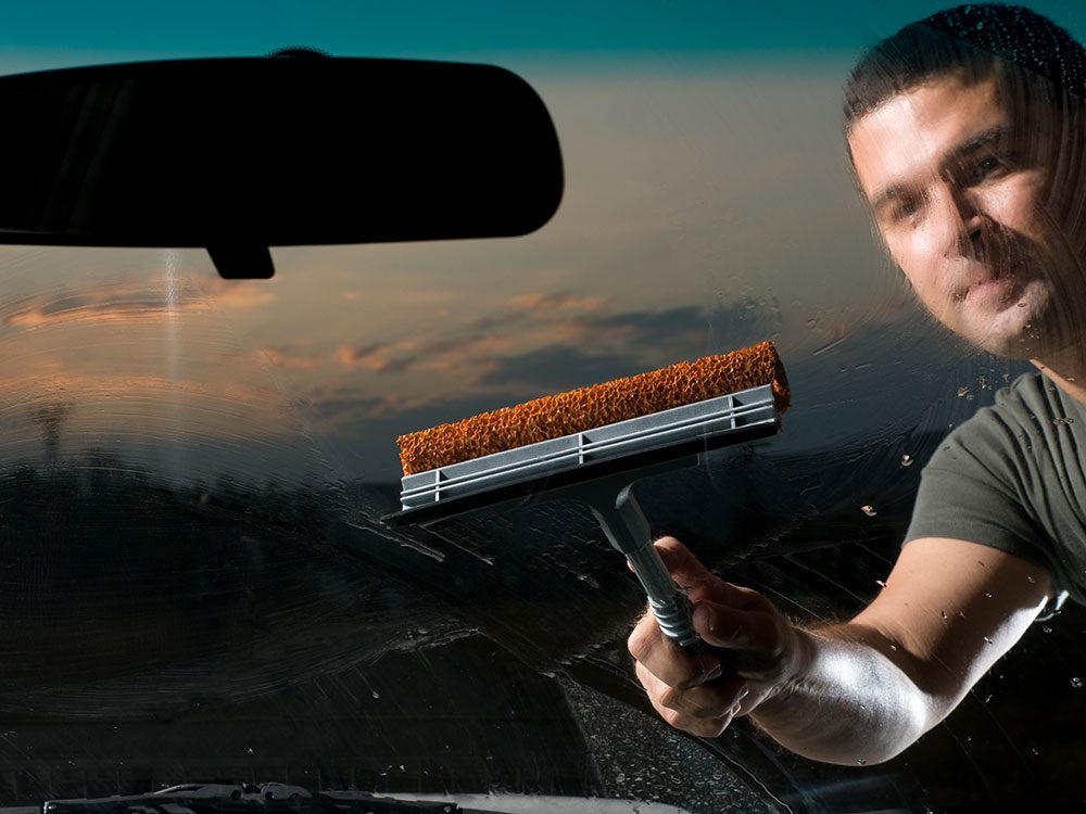 Man cleaning car windshield with club soda
