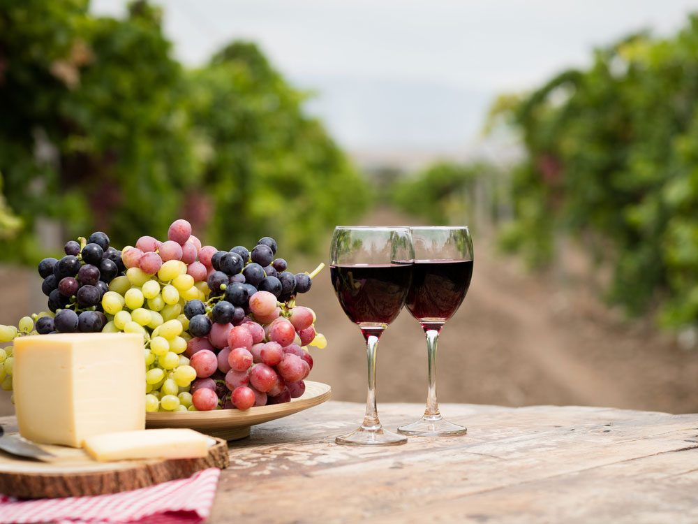 Wine on rustic wood table in vineyard