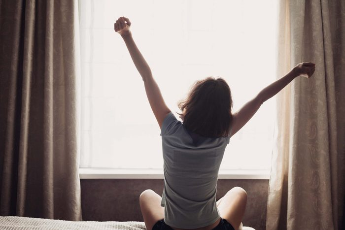 Woman stretching on her bed in the morning