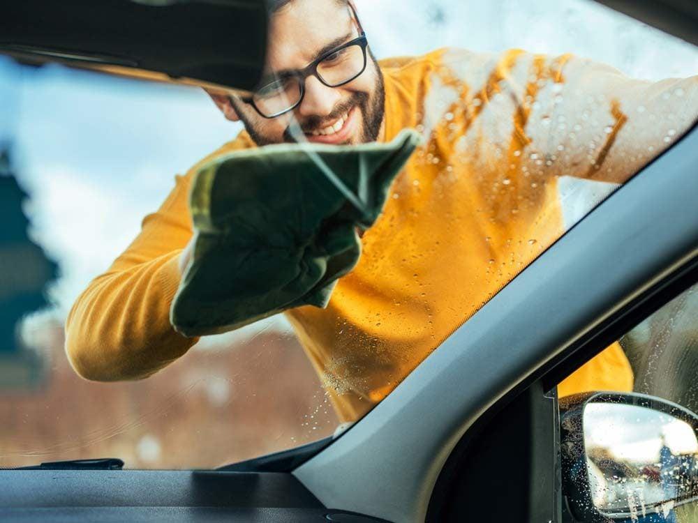 Man wiping his car windshield