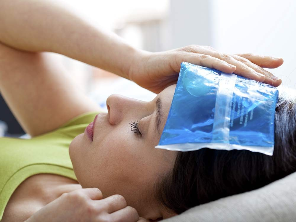Woman with ice pack on her forehead
