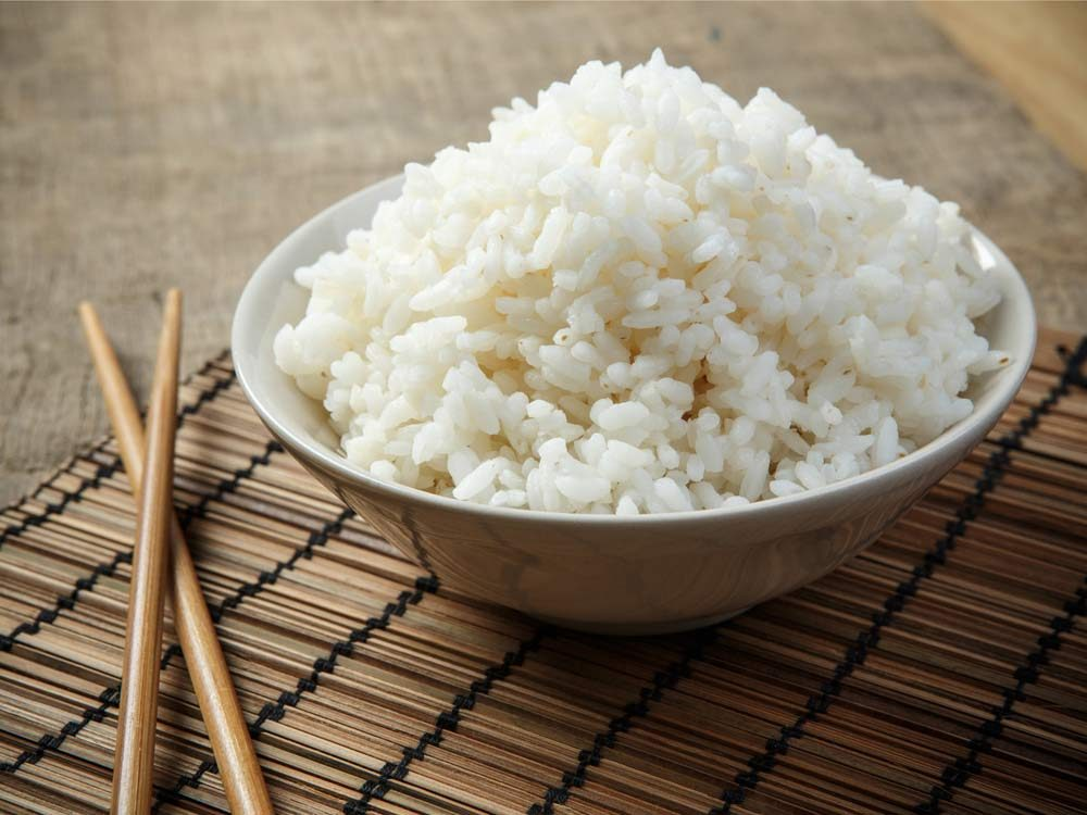 Chopsticks and bowl of rice on bamboo mat