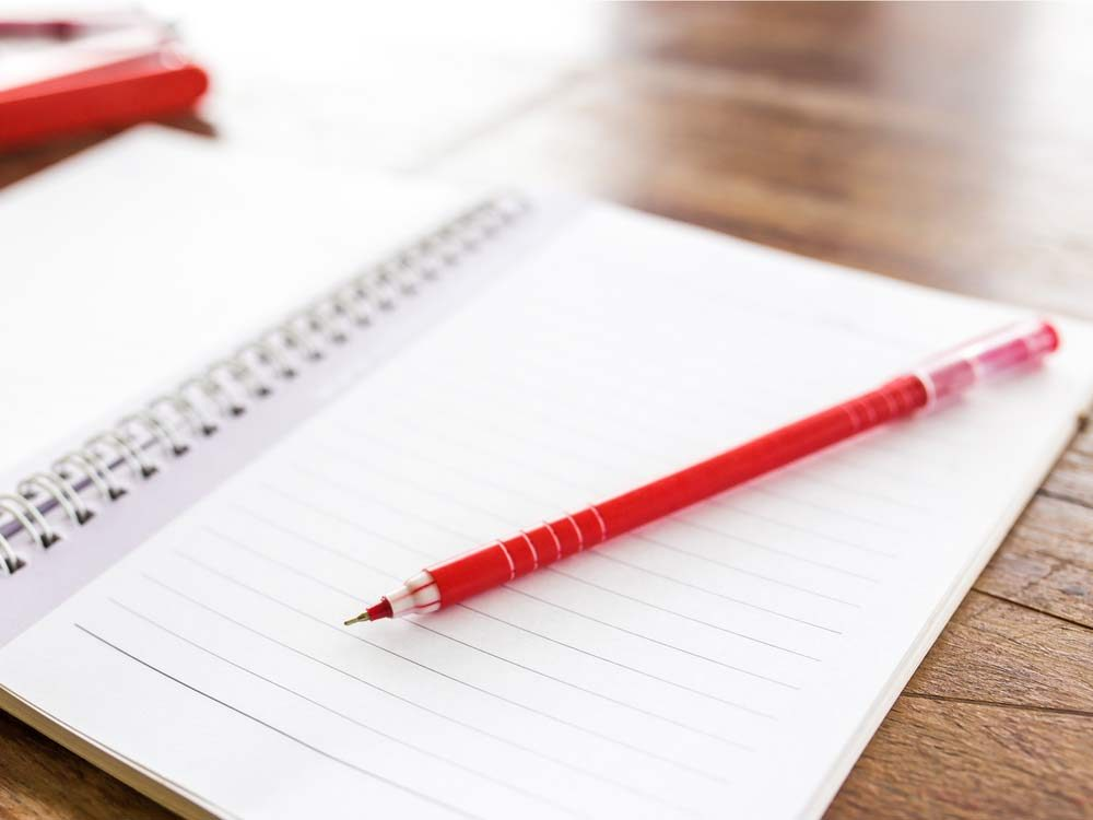 Red pen and white notebook