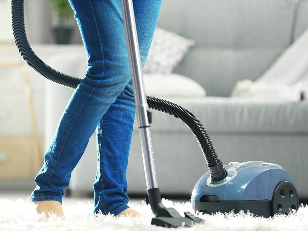 Woman vacuuming her living room carpet