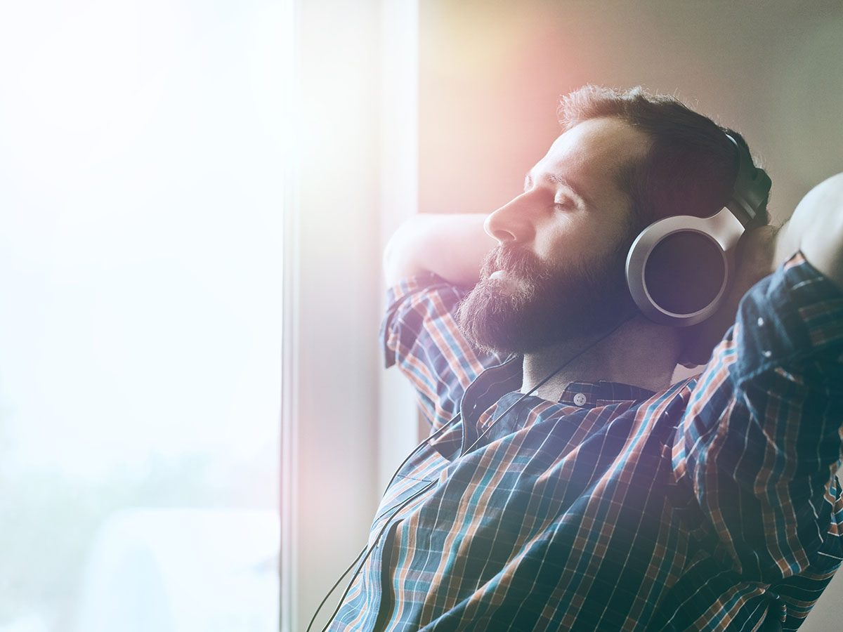Stress management tips - Man listening to music using headphones