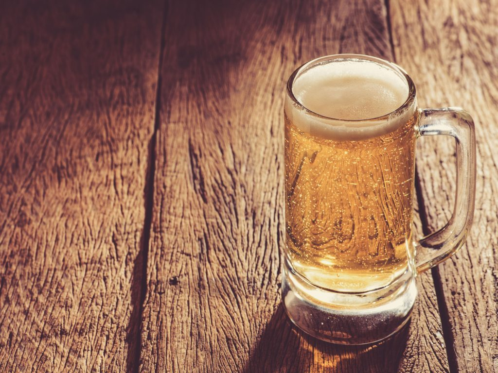 A cold glass of beer on a wooden table