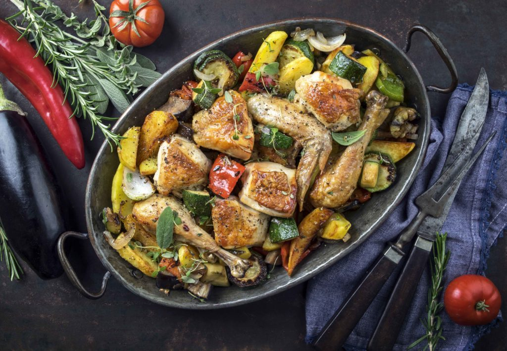 Chicken pieces roasting in pan with vegetables