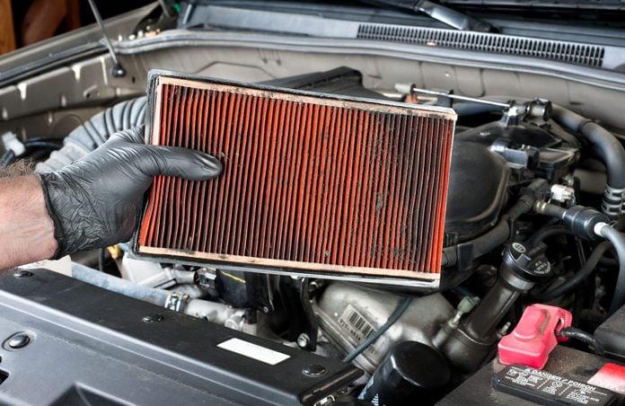 Man checking car air filter