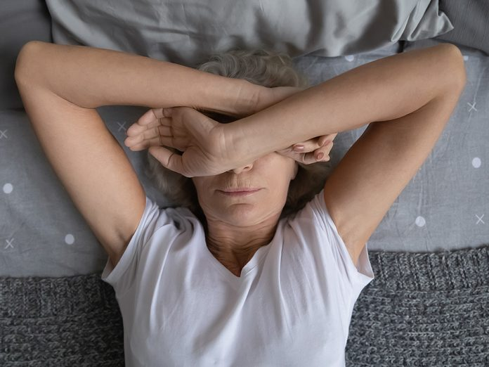 Top view aged woman lying on bed woke up at night due noisy neighbors. Mature female cover face with hands suffers from insomnia sleep disorder, has restless obsessive thoughts keep her awake concept