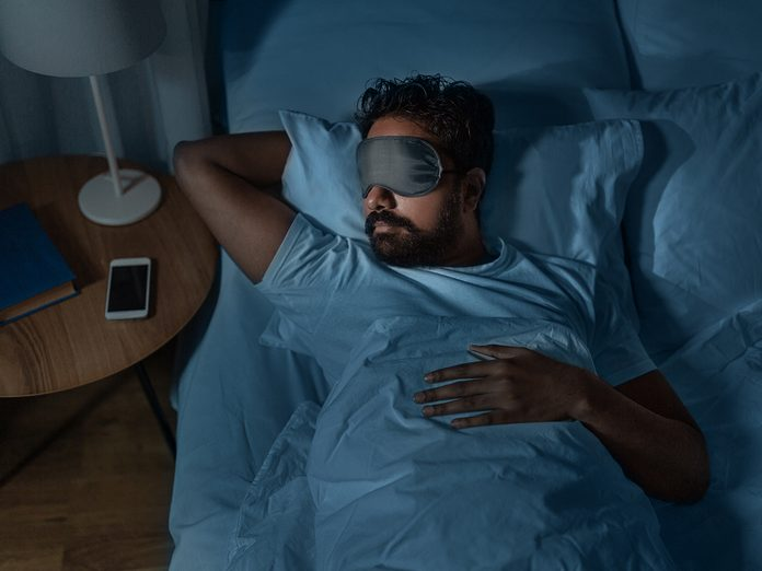 people, bedtime and rest concept - indian man in eye mask sleeping in bed at home at night