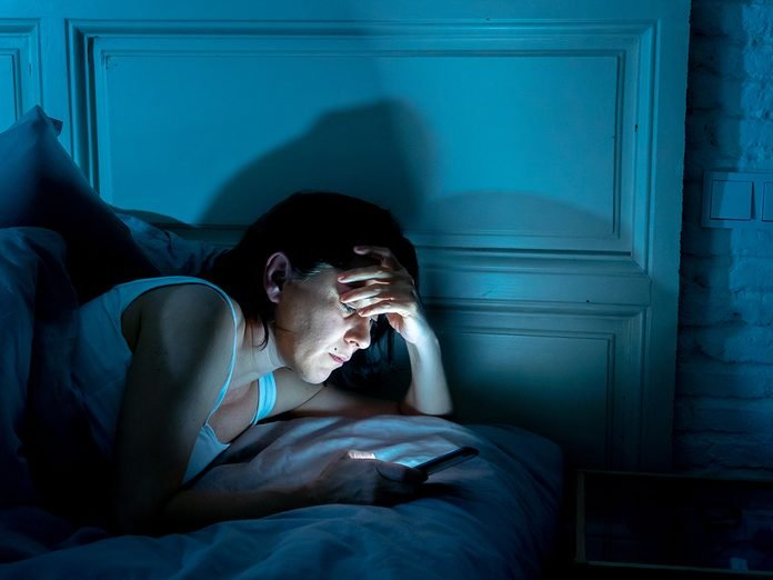 Young attractive woman awake late at night using smart phone lying in bed in a dark bedroom. Using mobile for chatting and sending messages in internet addiction, mobile abuse and insomnia concept