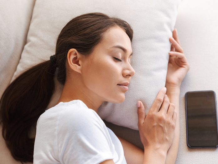 Top view of a pretty young asian woman sleeping on couch at home with blank screen mobile phone