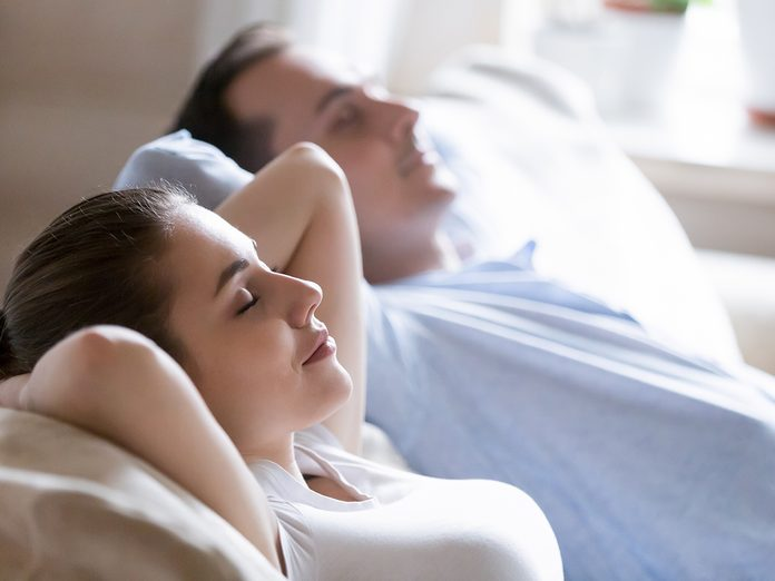Close up of mindful husband and wife sleeping on sofa relaxing hands over head, calm man and woman lying on cozy couch taking nap at home, millennial couple enjoying rest with eyes closed dreaming
