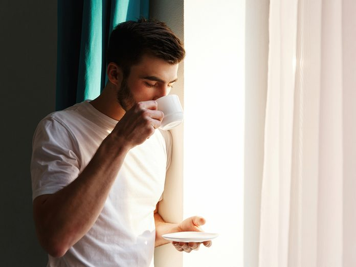 Handsome brunette bearded man stands before bright window and drinks coffee