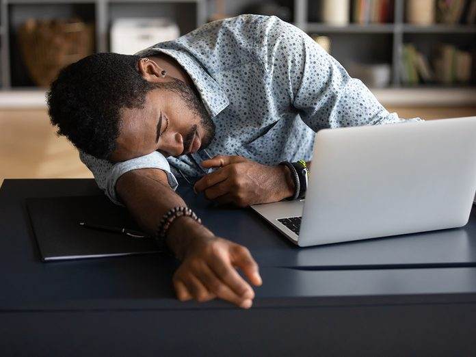 Exhausted tired African American businessman entrepreneur lying on desk with closed eyes, falling asleep, overworked young man unmotivated student sleeping at workplace, boring routine work