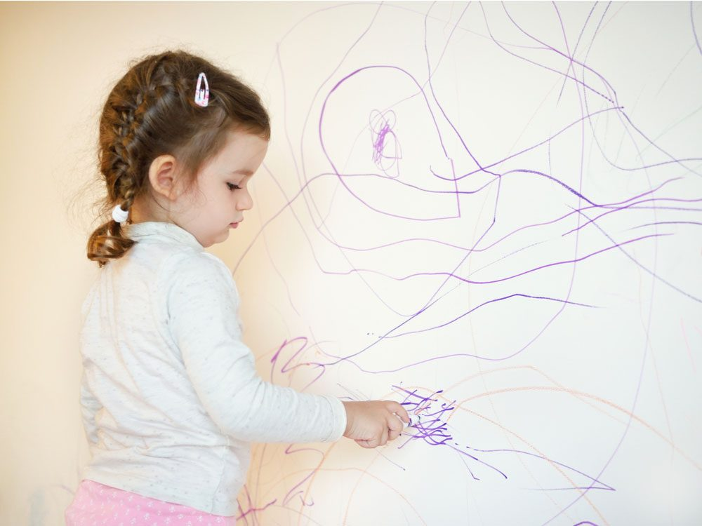 Little girl drawing on wall with crayon