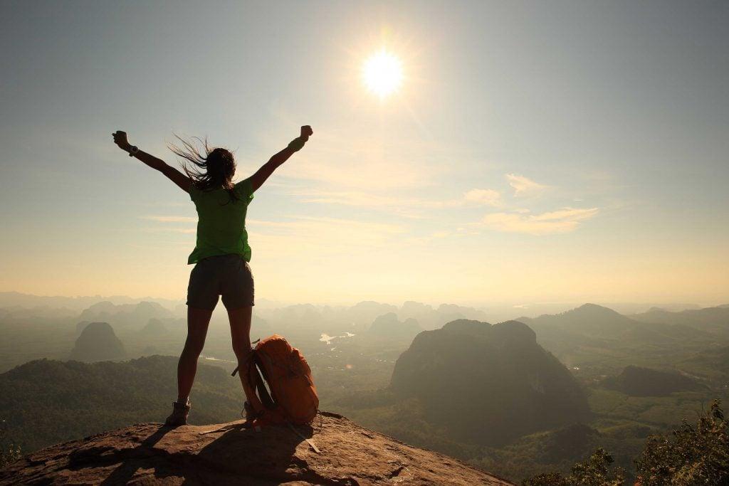 Confident woman cheering on mountain peak