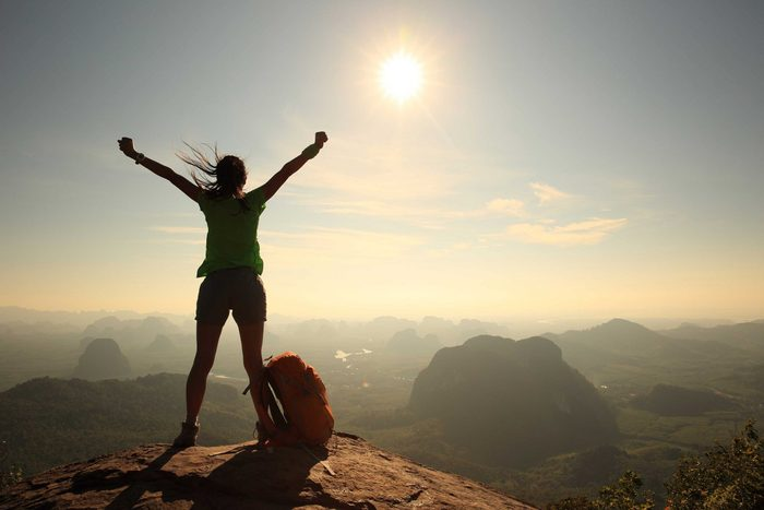 Confidence lessons - Confident woman cheering on mountain peak