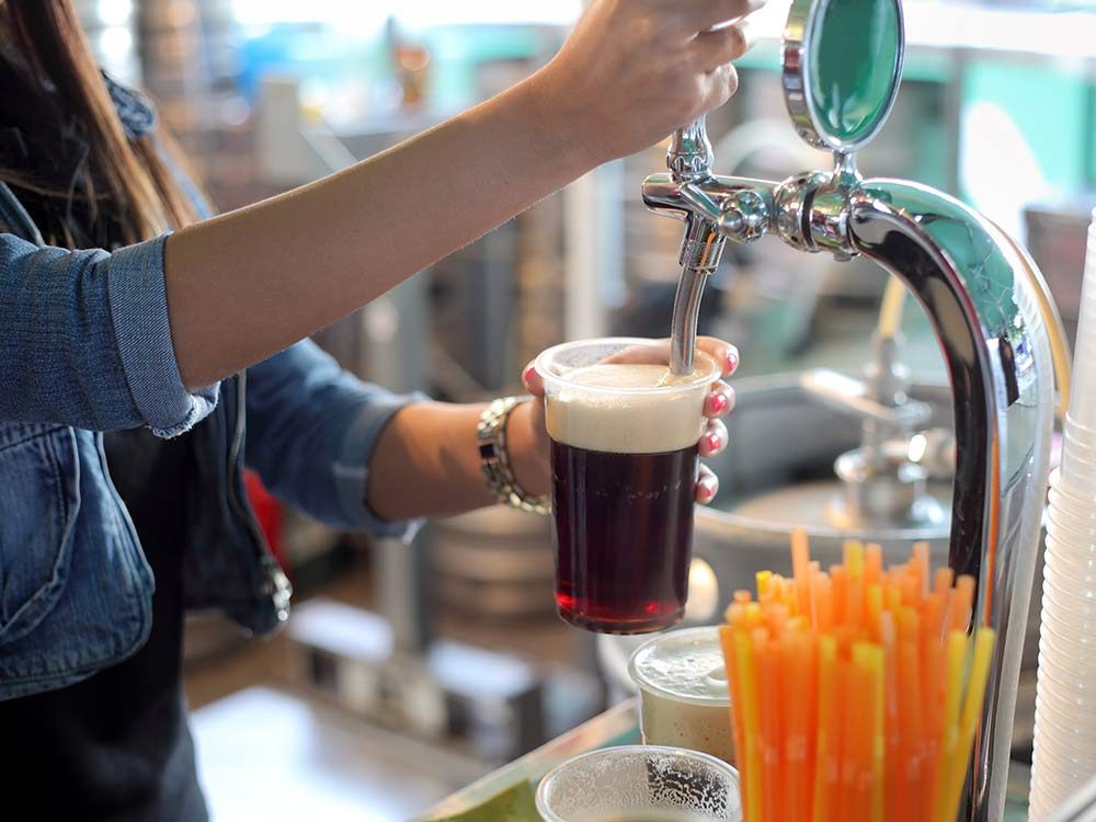 Woman serving beer from tap in England