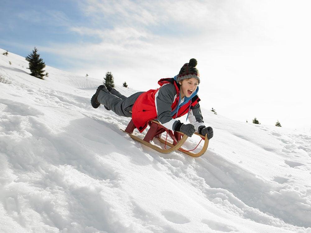 Boy sledding down hill