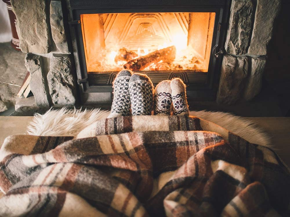 Couple cozying up to fireplace