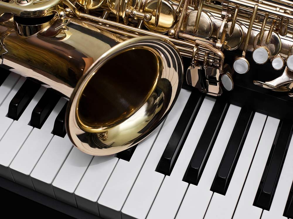 Gold saxophone lying on piano keys
