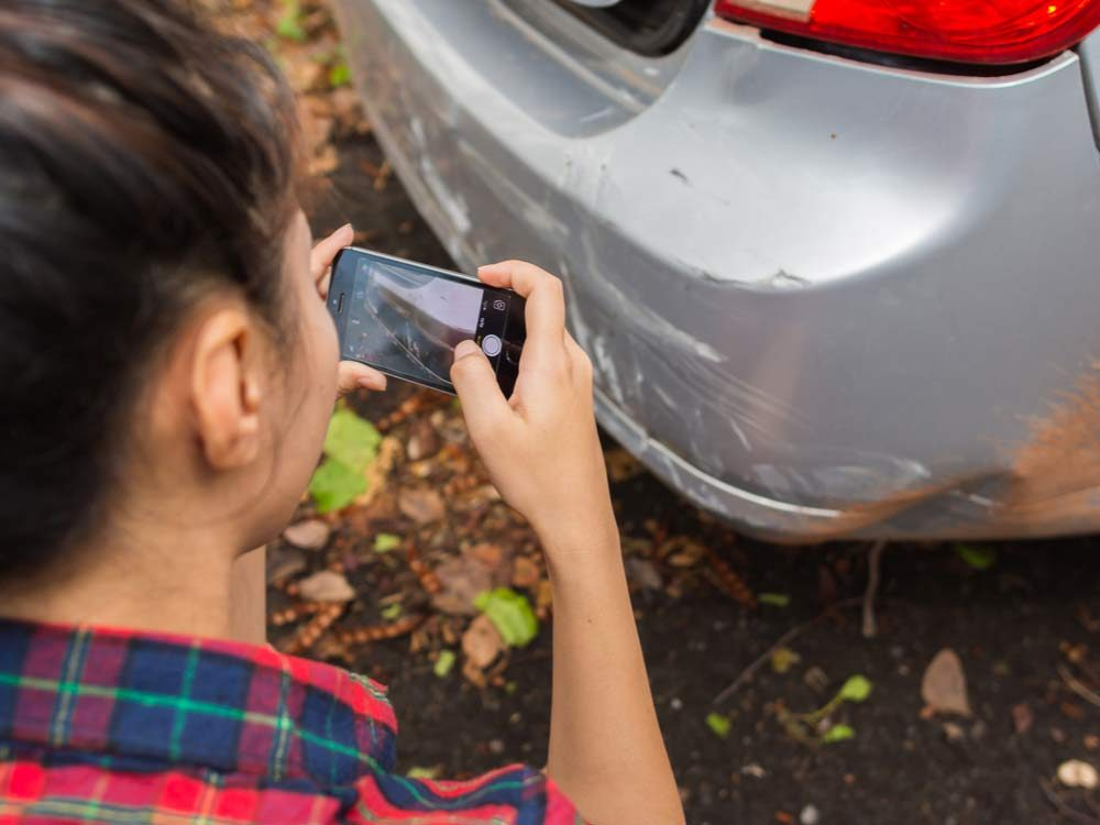 Young woman photographing damage on car