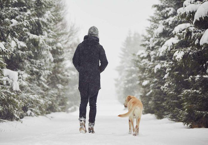 Woman walking dog outdoors in winter