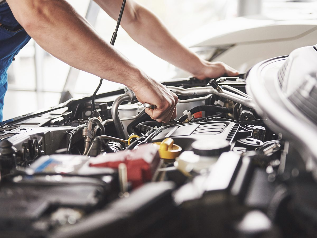Mistakes that devalue your car - mechanic working under hood
