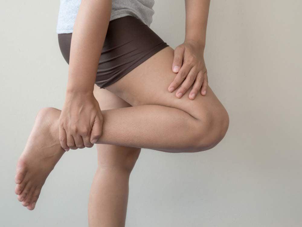 Woman massaging her leg calf