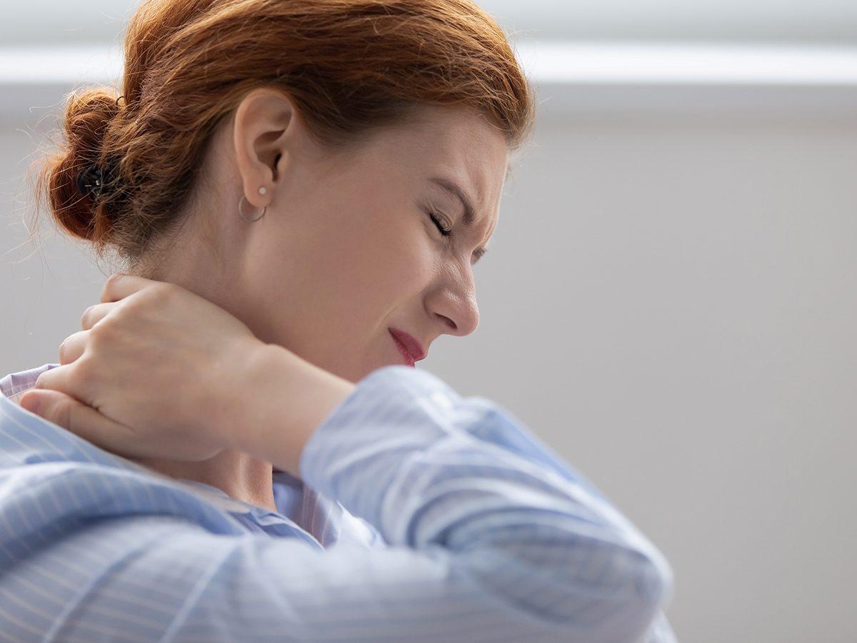 Stiff neck remedies - woman suffering stiff neck