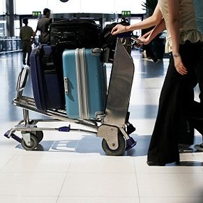 Carrying luggage on a cart.