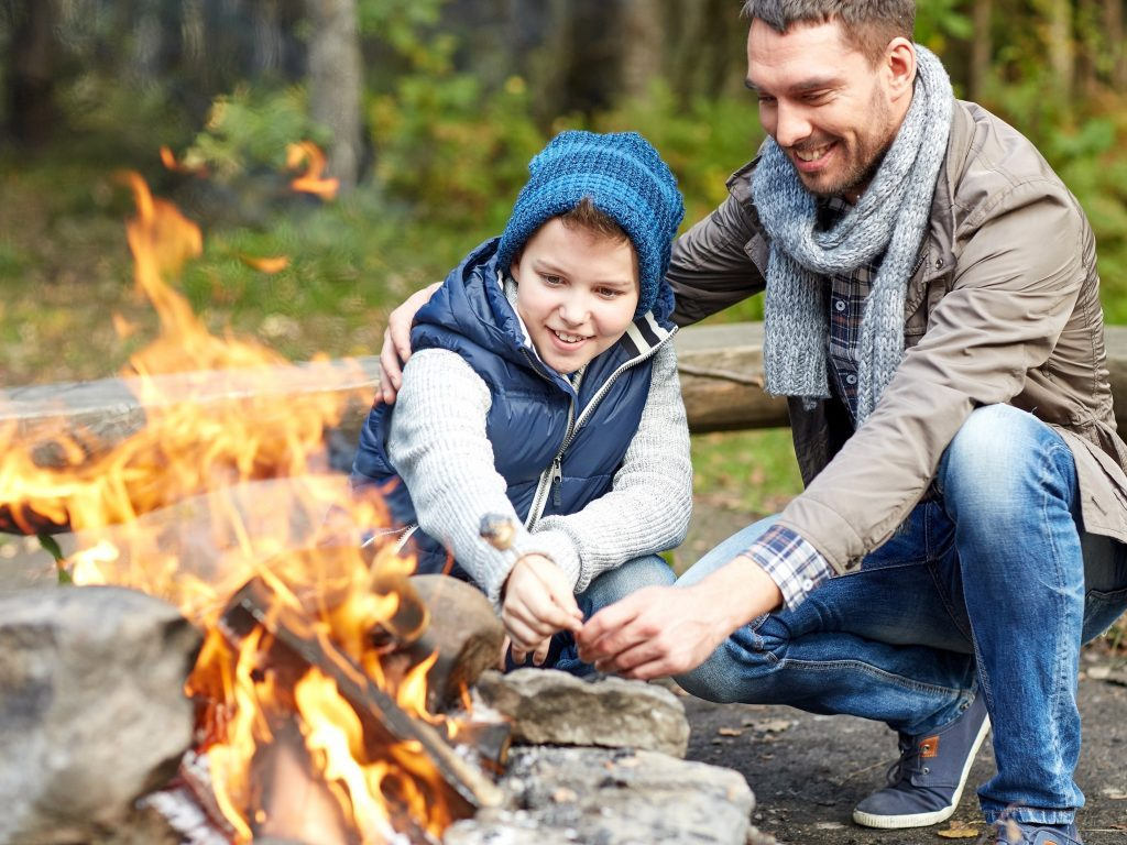 Father and son lighting a fire