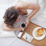 Woman eating breakfast in bed