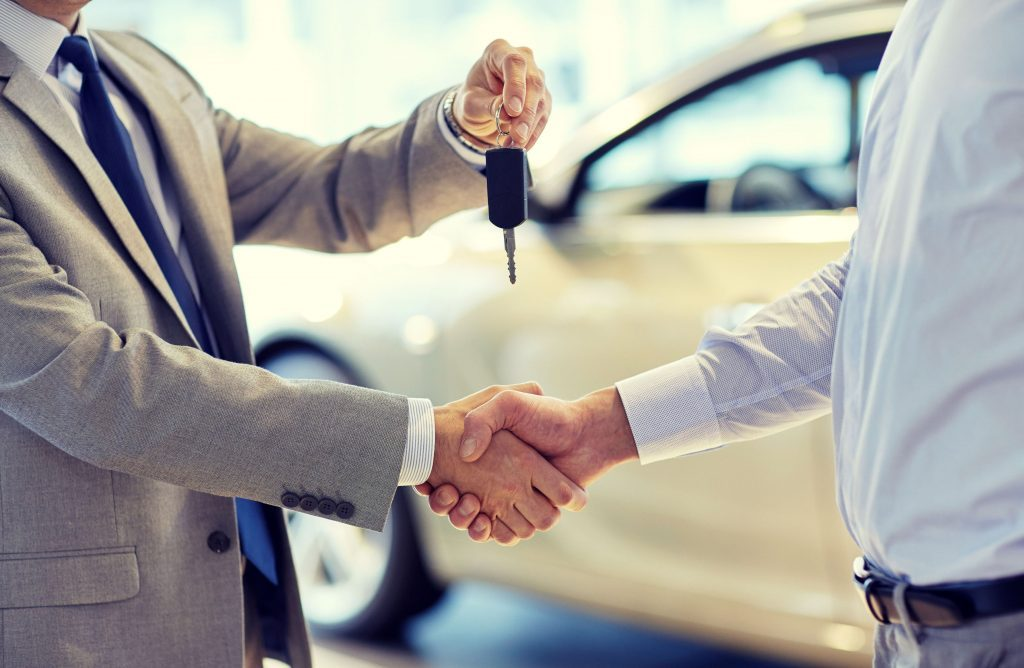 Car salesman giving keys to customer