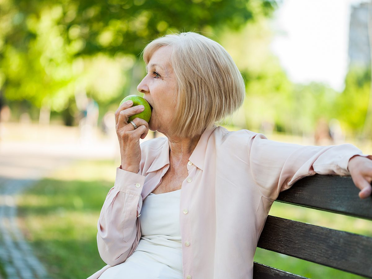 Apple benefits - mature woman eating apple