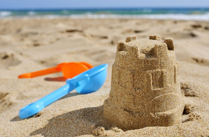 Sandcastle surrounded by toys at beach