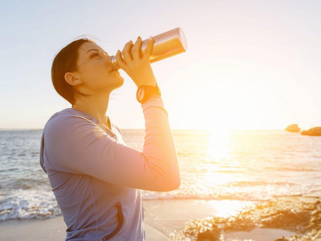 Woman drinking from water bottle on beach