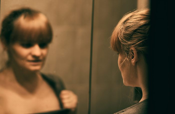 Woman unhappy while looking at herself in mirror