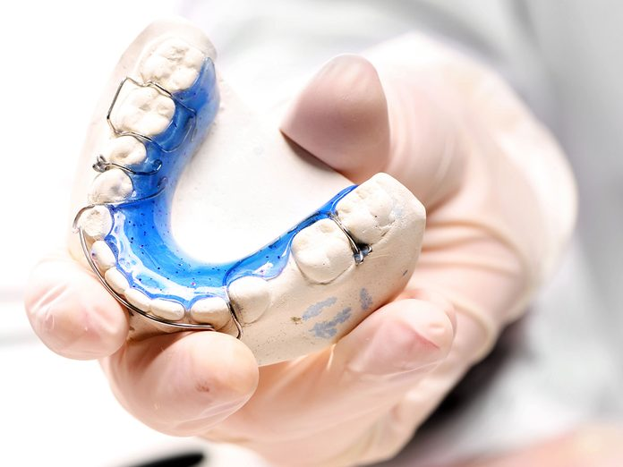 Orthodontist fitting a retainer