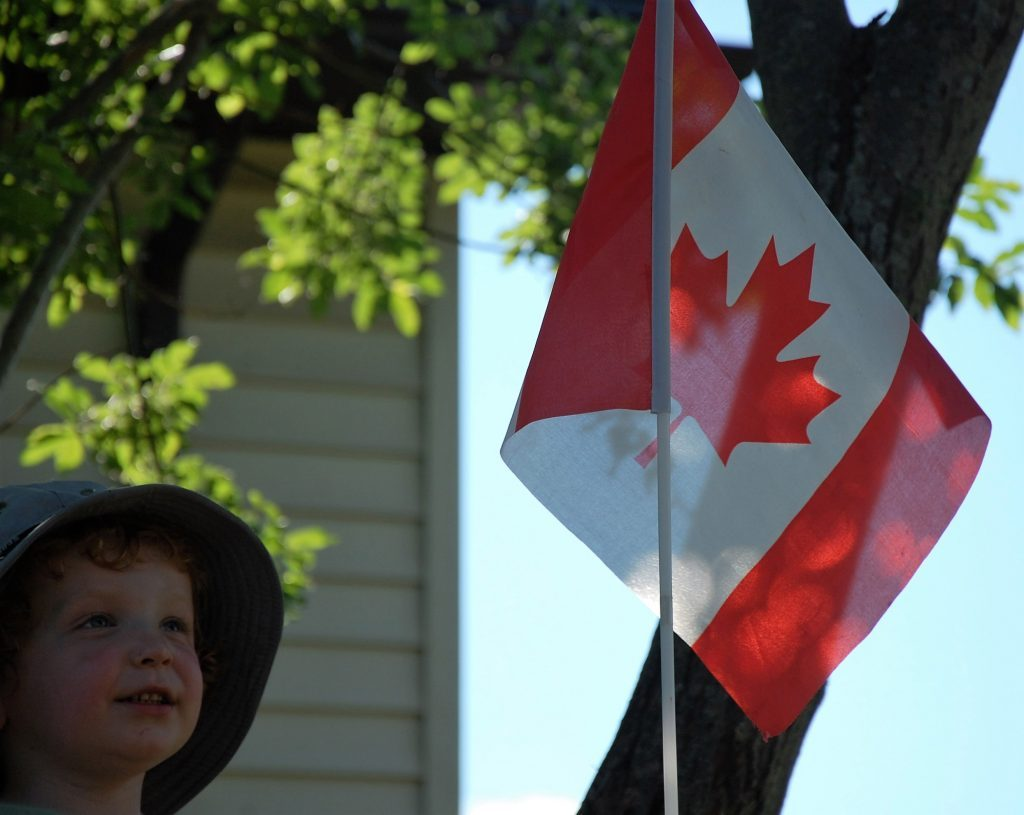 Boy next to Canadian flag at the cottage