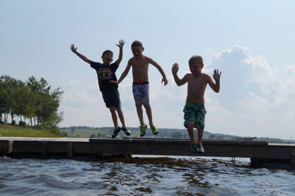 Three boys jumping into the lake at the cottage