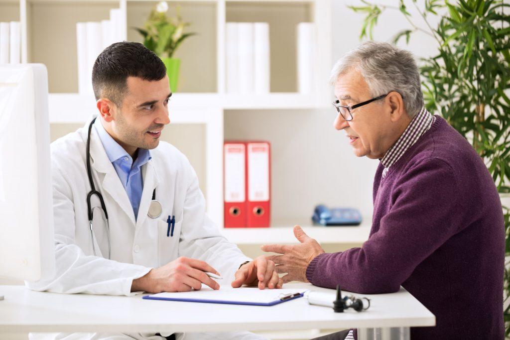 Elderly patient talking to doctor