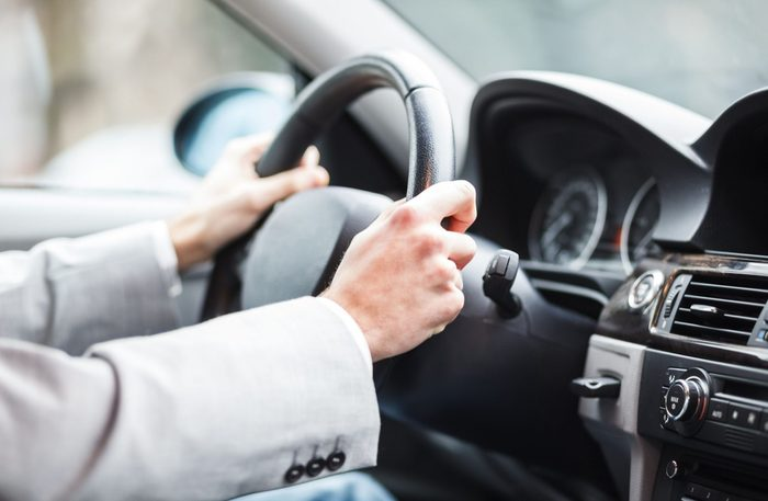 Close-up of hands on steering wheel