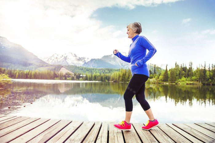 Senior woman walking next to lake