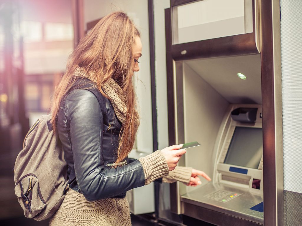 Post-secondary student withdrawing her savings from an ATM